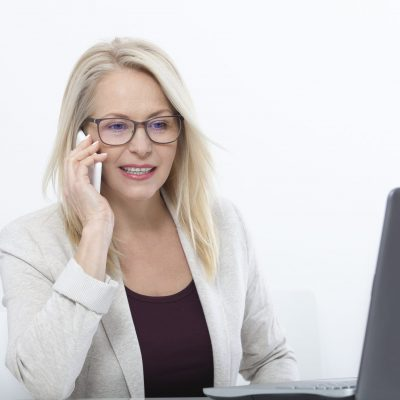 Happy businesswoman working and chating with laptop at office