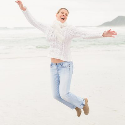 Woman jumping into the air at the beach